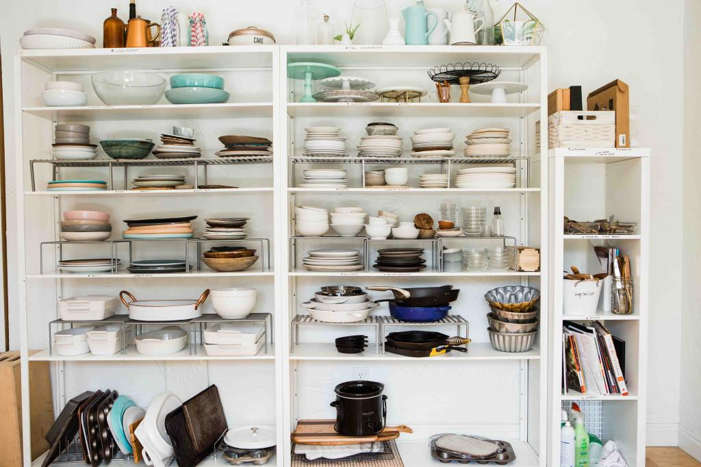 A set of two doorless kitchen cabinets full of various sizes and types of dishes.