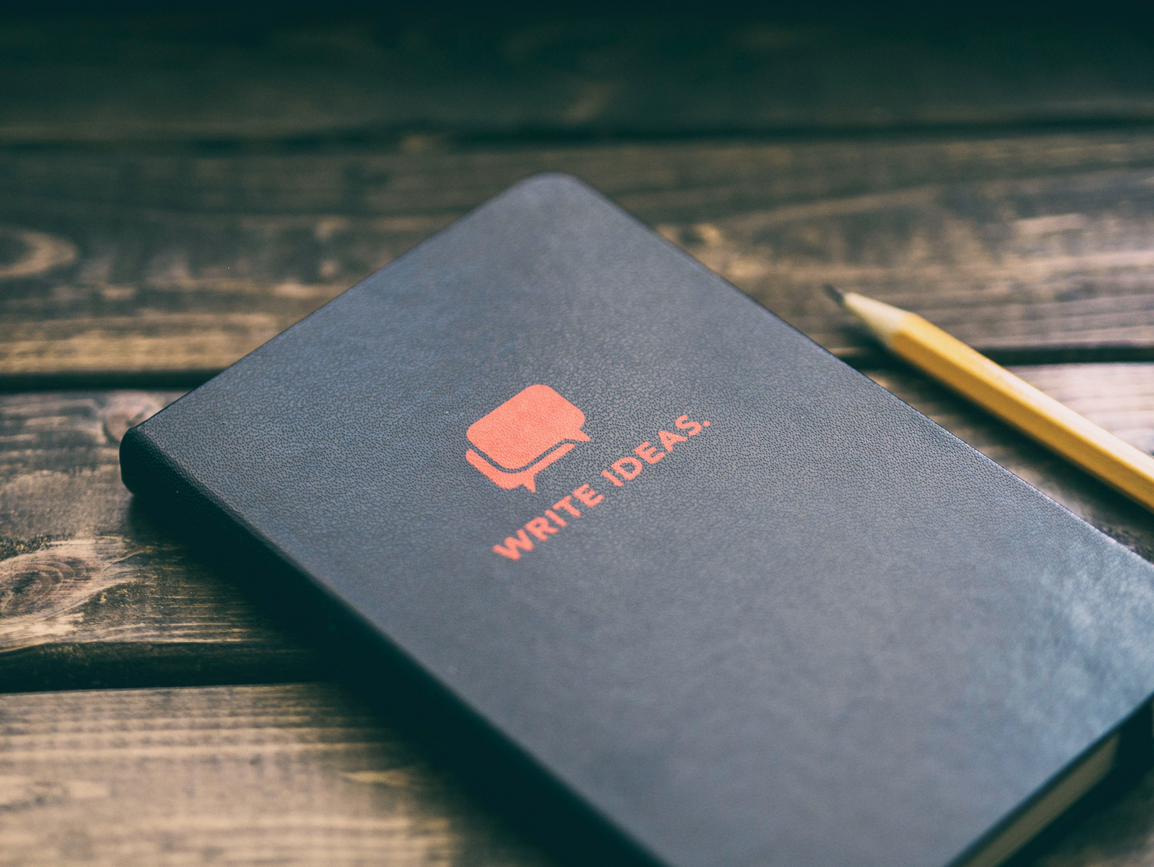 "A black notebook with red writing that says ""Write Ideas"" with two overlapping speech bubbles. Next to the notebook is a wooden pencil. The notebook and pencil are on top of a dark stained wooden surface with slats."