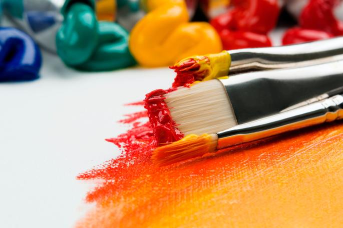 A close-up of three paintbrushes with thick acrylic paint in red and yellow shades. They are laying on a canvas with a red, orange, and yellow ombre. In the background, there are several tubes of paint with paint squeezed out, showing piles of acrylic paint in blue green, yellow, orange, and red hues.
