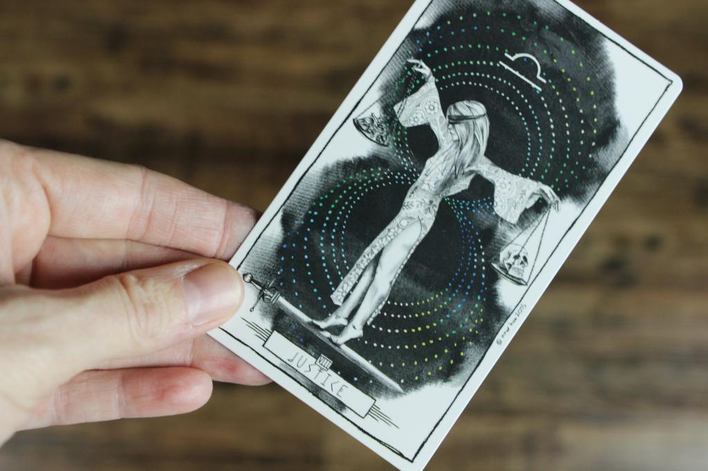 "A white person's hand holding a tarot card labeled ""Justice."" Justice is a blindfolded, thin, white-appearing feminine person wearing a blindfold and a floral patterned dress, standing on tiptoes on a sword. Justice has their arms outstretched and is holding a scale's plate in each hand, one holding a skull and the other holding what may be a human heart (the image is not close enough to make out clearly). Above Justice is the symbol for Libra."