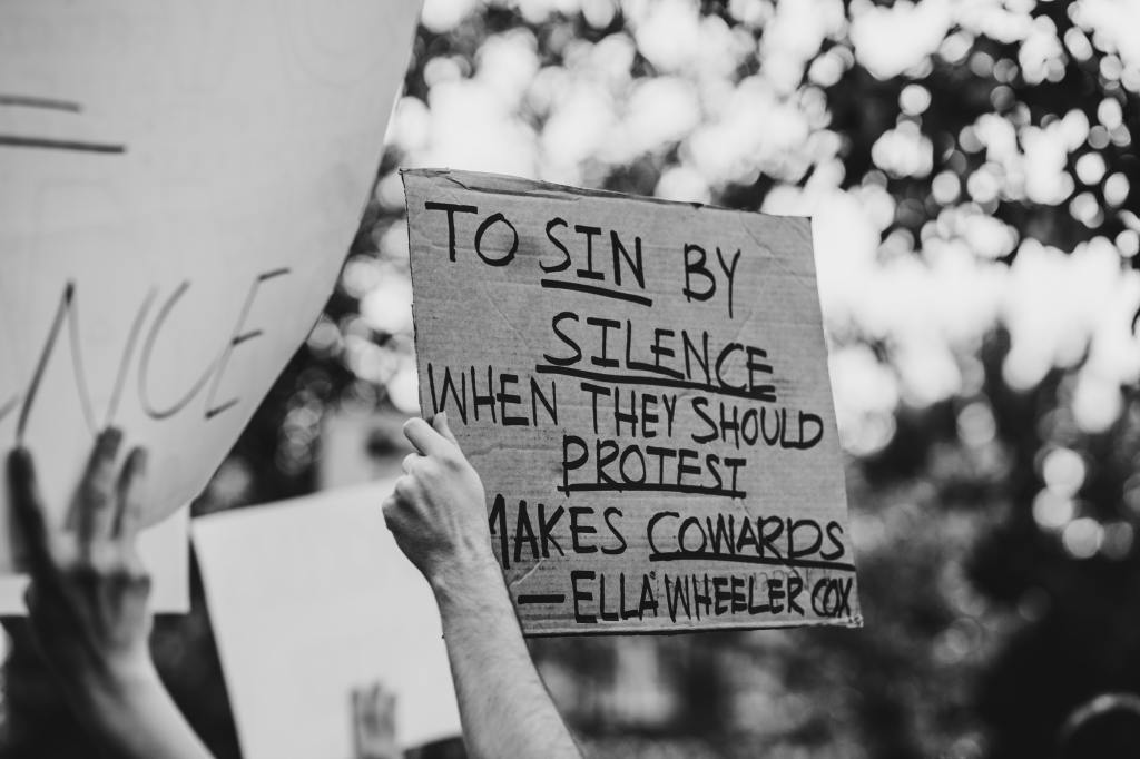 "Image Desc: A photo from a Black Lives Matter protest with signs unfocused in the foreground and background. A sign in the center, held up by a white-appearing person's arm, says ""To sin by silence when they should protest makes cowards - Ella Wheeler Cox"""