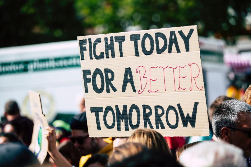 "A sign that says ""Fight today for a better tomorrow"" amidst several people at a protest."