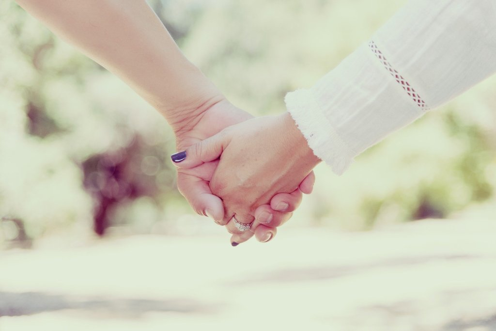 A close up of a couple holding hands. The hand on the left is white and has short, unpolished nails. The hand on the left is also white, wearing a diamond ring, and has purple nail polish. The arm on the right is wearing a white linen shirt.