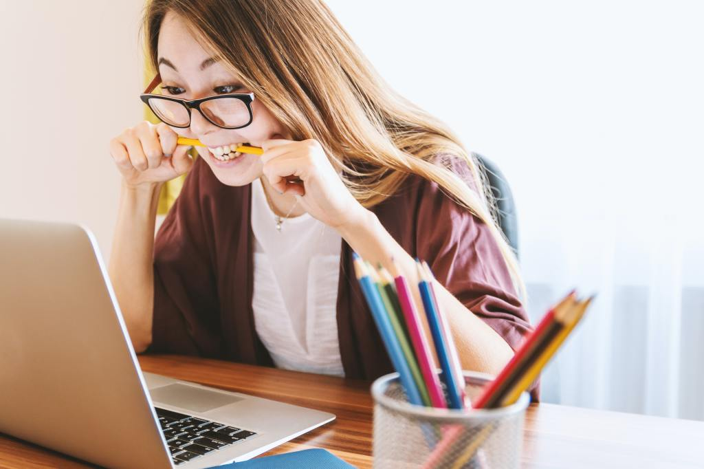 An image of a woman wearing glasses, stressfully chewing on a pencil as she looks at her laptop intently.