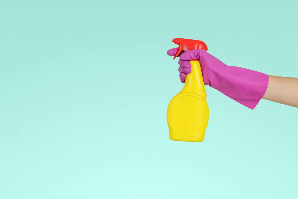 A light teal background with an arm coming in from the right. The arm is wearing a hot pink rubber glove and holding a yellow spray bottle with a red nozzle top.