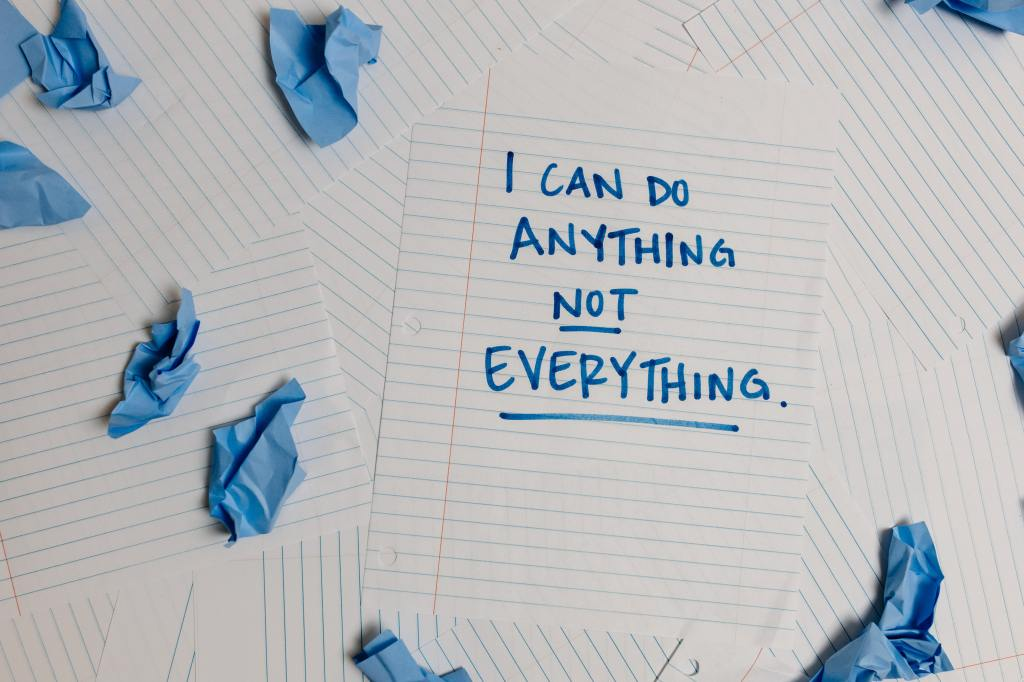 """The image background is several sheets of blank, lined notebook paper and pieces of crumpled blue paper. On one sheet of paper in blue marker is written """"I can do anything not everything."""""""